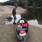 Charles téléphone près du canoë au bord de l'Ardèche