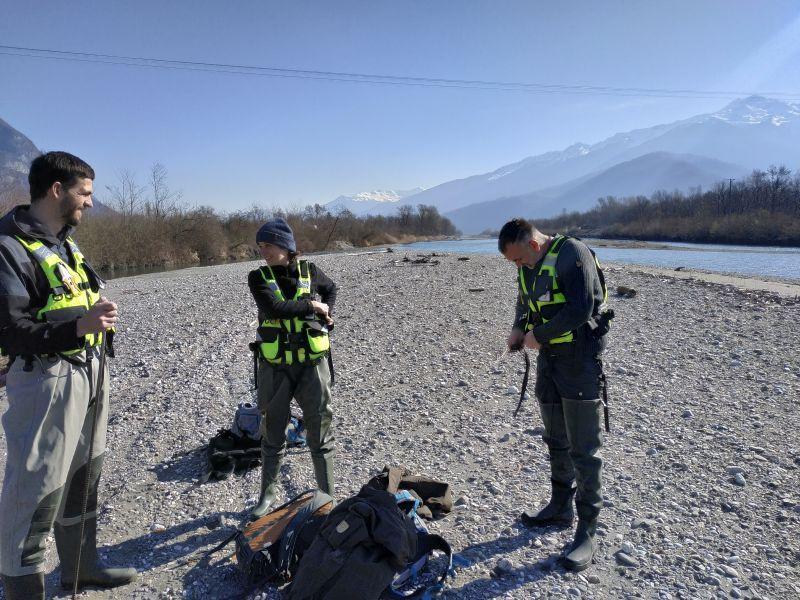 Photo d'une partie de l'équipe Dynamique Hydro (Alexia Chiavarino, Simon Chabbert, Loïc Grosprêtre) sur le terrain dans le lit de l'Isère. Conformément à notre protocole sécurité MASE, ils sont équipés notamment de gilets de sauvetage