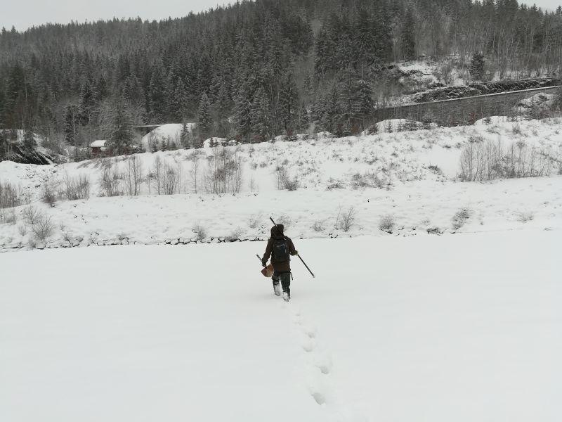 Loïc sous la neige portant une pelle pour creuser la neige à la recherche des parcelles peintes