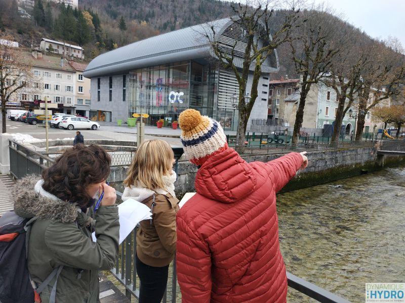 balade urbaine dans le cadre de la restauration écologique des berges de la Bienne dans le Jura. Photo d'une personne expliquant le fonctionnement hydraulique du cours d'eau