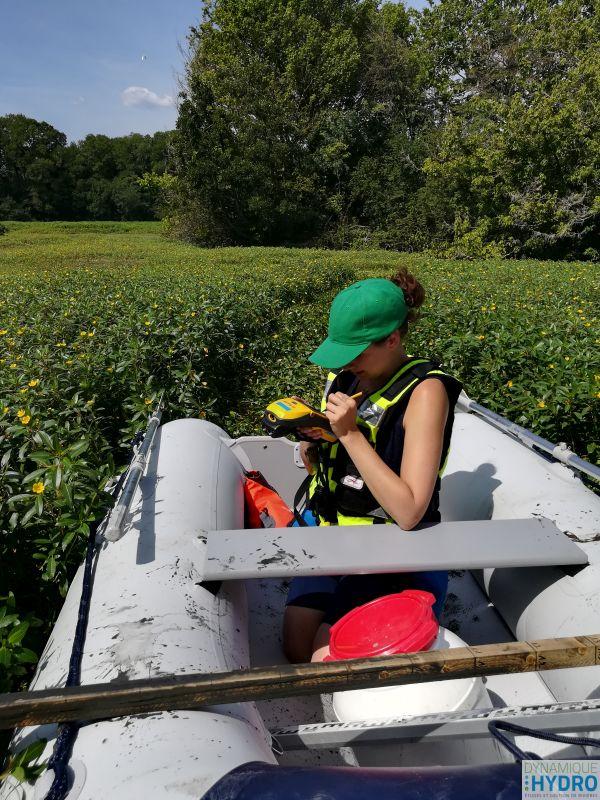 Alexia prend des points GPS (bathymétrie) dans un des lacs des zones humides des îles du Rhône dans la Drôme. Elle est assise dans notre bateau pneumatique Yam 275Sti
