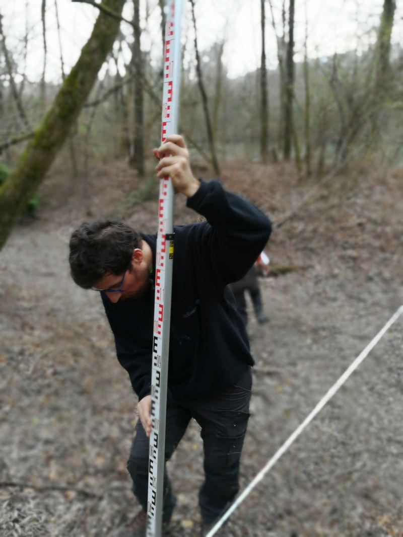 Suivi morphologique : Baadïs tient la mire de 5 mètres associées au niveau de chantier Leica NA720 sur une annexe de l'Isère