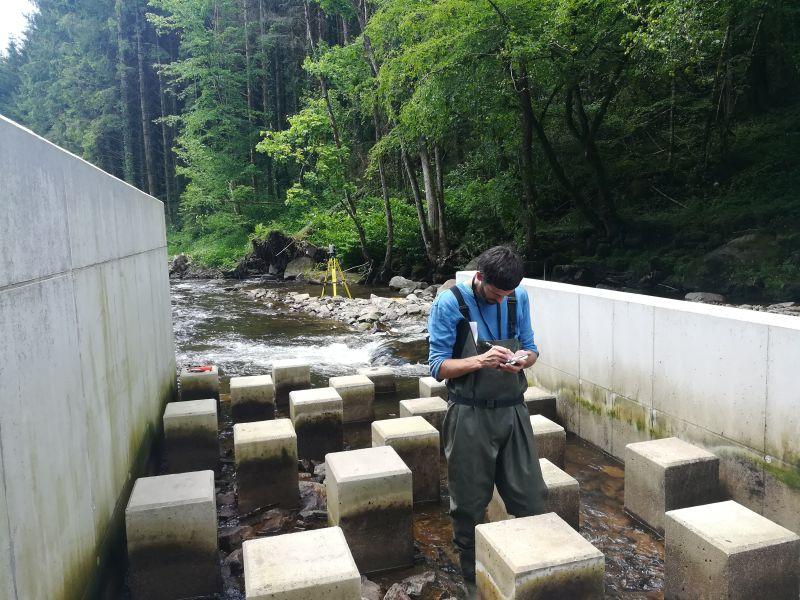 Simon dans la passe à poisson, mire à la main pour les relevés topographiques du plan de récolement