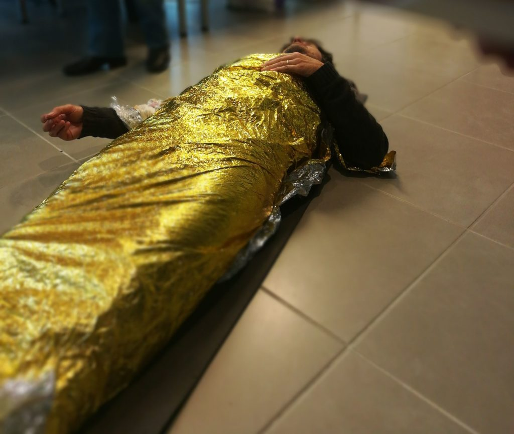Photo de mise en situation : mise en place d'une couverture de survie lors de notre formation SST (sauveteur secouriste du travail)